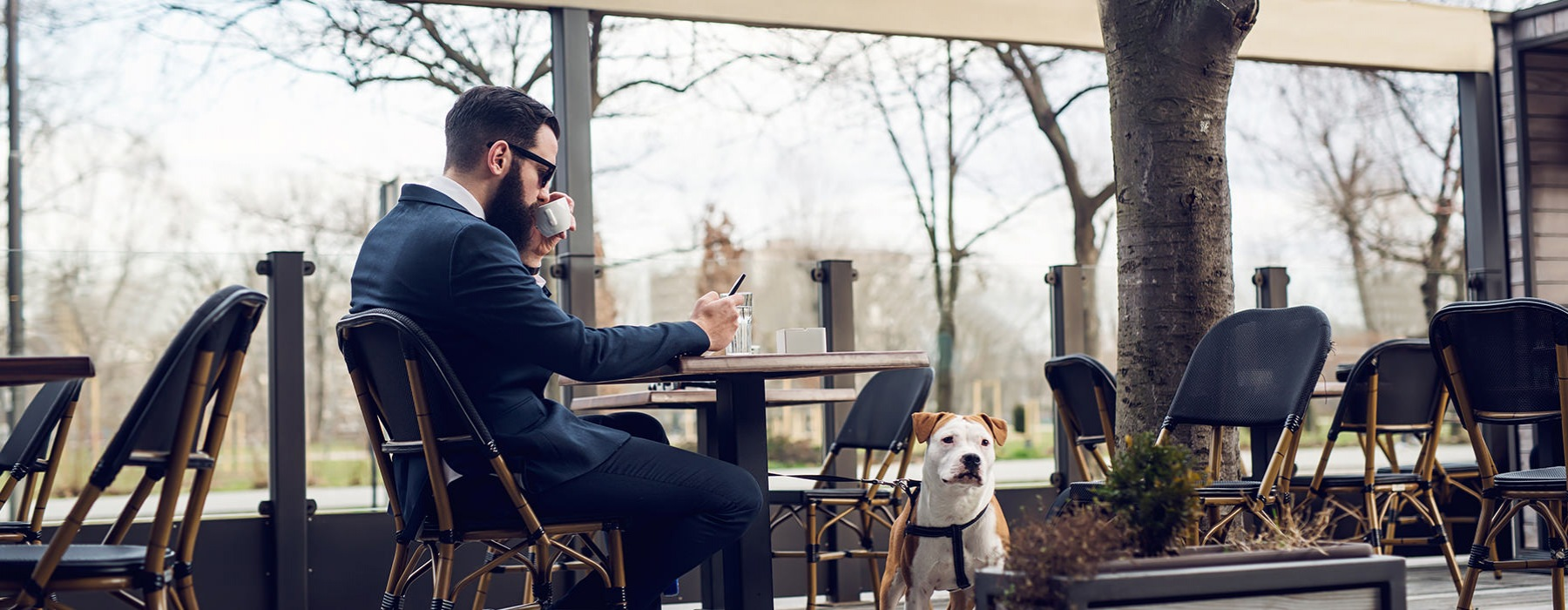 man drinking coffee with dog